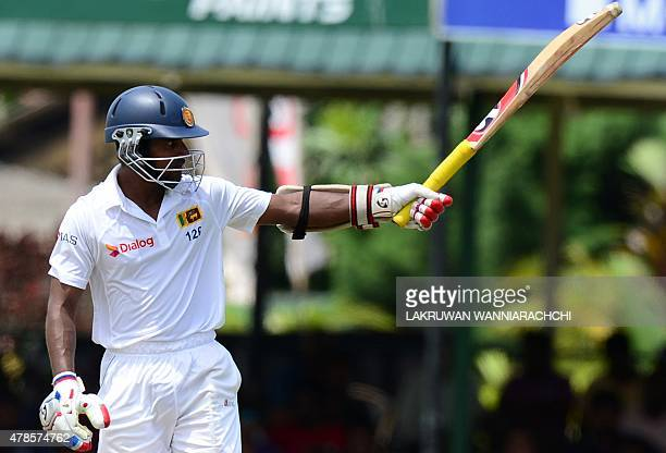 Sri Lankan cricketer Kaushal Silva raises his bat to the crowd after scoring a halfcentury during the second day of the second Test cricket match...