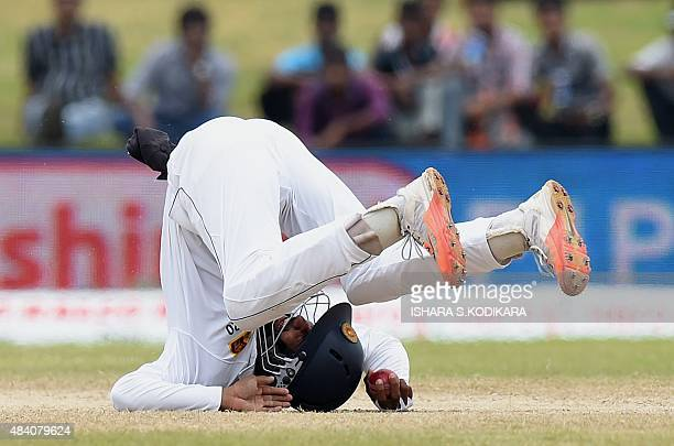 Sri Lankan cricketer Kaushal Silva takes a catch to dismiss Indian batsman Harbhajan Singh during the fourth day of the opening Test match between...