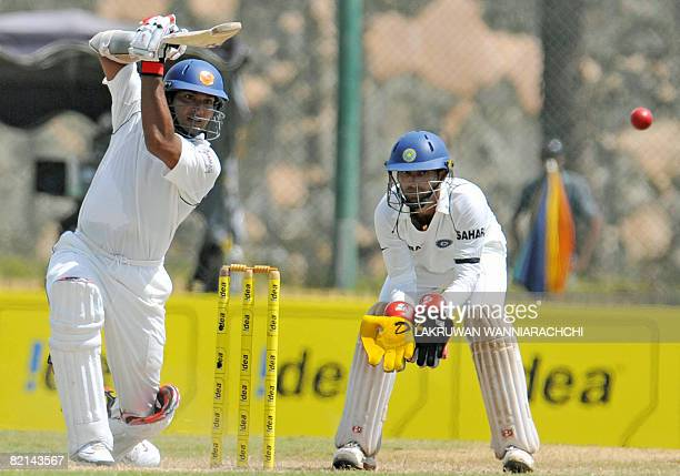 Sri Lankan cricketer Kumar Sangakkara is watched by Indian wicketkeeper Dinesh Karthik as he plays a stroke during the second day of the second Test...