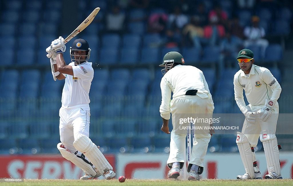 Sri Lankan cricketer Kumar Sangakkara (L) plays a shot as Bangladeshi wicketkeeper and captain Mushfiqur Rahim (R) looks on during the fourth day of the second Test match between Sri Lanka and Bangladesh at the R. Premadasa Cricket Stadium in Colombo on March 19, 2013.