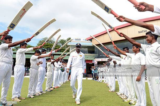 Sri Lankan cricketer Kumar Sangakkara walks through an 'archway of cricket bats' as he goes out to field during the opening day of their second Test...