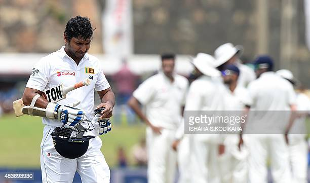 Sri Lankan cricketer Kumar Sangakkara walks to the pavilion after his dismissal during the first day of the opening Test cricket match between Sri...