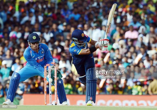 TOPSHOT Sri Lankan cricketer Kusal Mendis gets dismissed by Indian spinner Axar Patel as wicketkeeper Mahendra Singh Dhoni look on during the first...