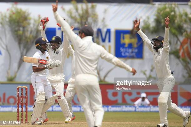 Sri Lankan cricketer Kusal Mendis looks at the umpire as Indian closein fielders appeal for his wicket during the 4th Day's play in the 1st Test...