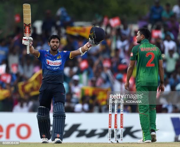 Sri Lankan cricketer Kusal Mendis raises his bat in celebration after scoring a century as Bangladesh cricket captain Mashrafe Mortaza looks on...