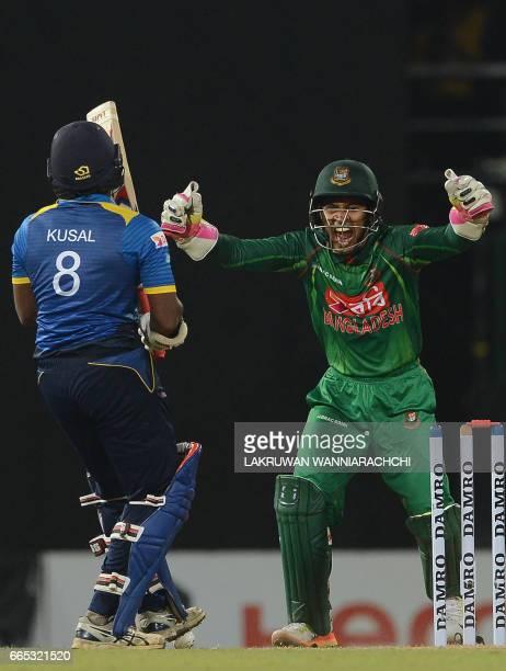 Sri Lankan cricketer Kusal Perera gets dismissed by Bangladesh cricketer Shakib Al Hasan as wicketkeeper Mushfiqur Rahim looks on during the second...