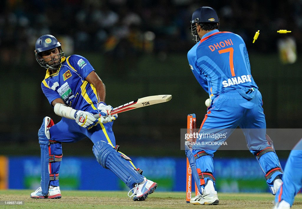 Sri Lankan cricketer Lahiru Thirimanne (L) gets dismissed as Indian cricket team captain Mahendra Singh Dhoni (R) looks on during a Twenty20 match between Sri Lanka and India at the Pallekele International Cricket Stadium in Pallekele on August 7, 2012. AFP PHOTO/ Ishara S