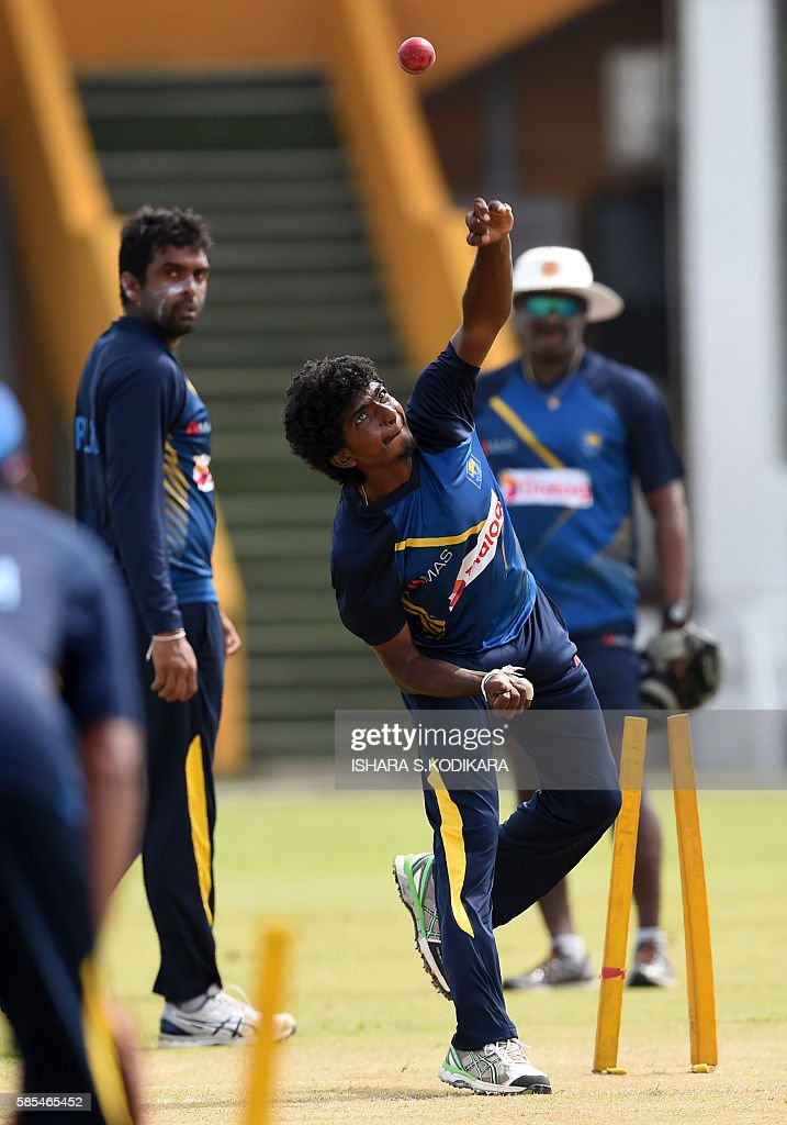 Sri Lankan cricketer Lakshan Sandakan delivers a ball as Dilruwan Perera looks on during a practice session at The Galle International Cricket...