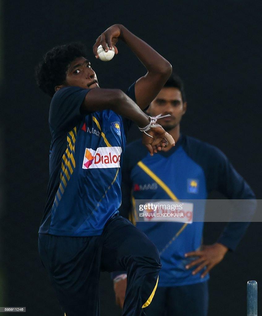 Sri Lankan cricketer Lakshan Sandakan delivers a ball as teammate Dhananjaya de Silva looks on during a practice session at The Rangiri Dambulla...