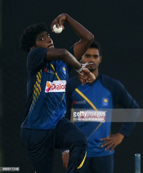 Sri Lankan cricketer Lakshan Sandakan delivers a ball as teammate Dhananjaya de Silva looks on during a practice session at The Rangiri Dambulla...