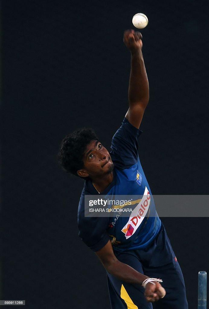 Sri Lankan cricketer Lakshan Sandakan delivers a ball during a practice session at The Rangiri Dambulla International Cricket stadium in Dambulla on...