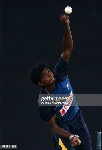 Sri Lankan cricketer Lakshan Sandakan delivers a ball during a practice session at The Rangiri Dambulla International Cricket stadium in Dambulla on...