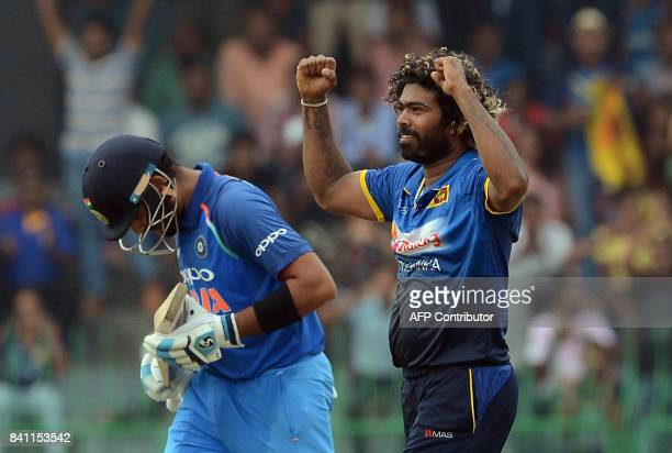 Sri Lankan cricketer Lasith Malinga celebrates after he dismissed Indian cricket captain Virat Kohli during the fourth one day international cricket...