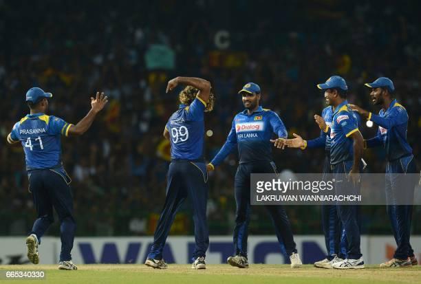 Sri Lankan cricketer Lasith Malinga celebrates with his teammates after taking a hat trick wicket to dismiss Bangladesh cricketer Mehedi Hasan during...