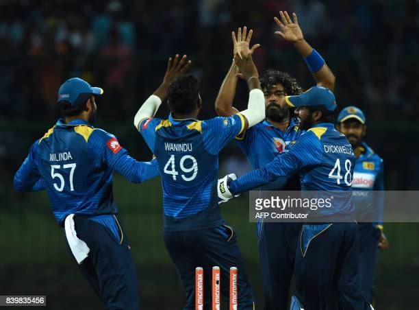 Sri Lankan cricketer Lasith Malinga celebrates with his teammates after he dismissed Indian batsman Shikar Dhawan during the third one day...
