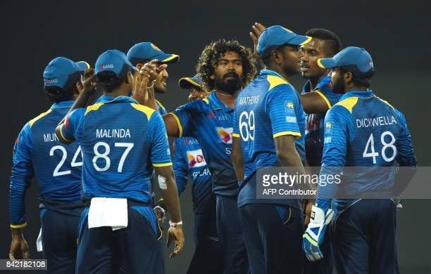 Sri Lankan cricketer Lasith Malinga celebrates with his teammates after he dismissed Indian cricketer Ajinkya Rahane during the final one day...