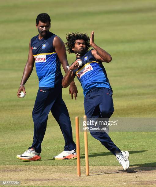 Sri Lankan cricketer Lasith Malinga delivers a ball as teammate Thisara Perera looks on during a practice session at the Pallekele International...