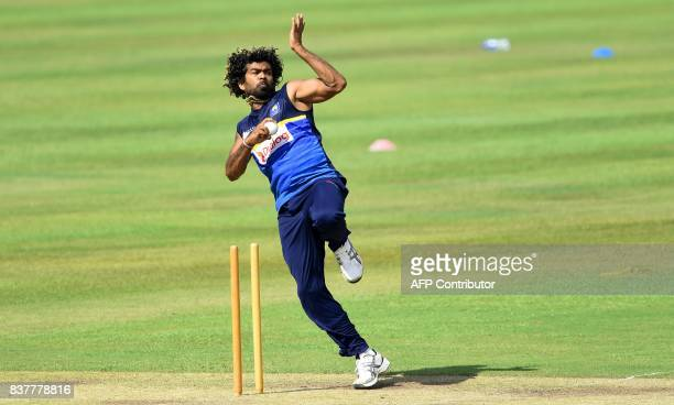 Sri Lankan cricketer Lasith Malinga delivers the ball during a practice session at the Pallekele International Cricket Stadium in Pallekele on August...