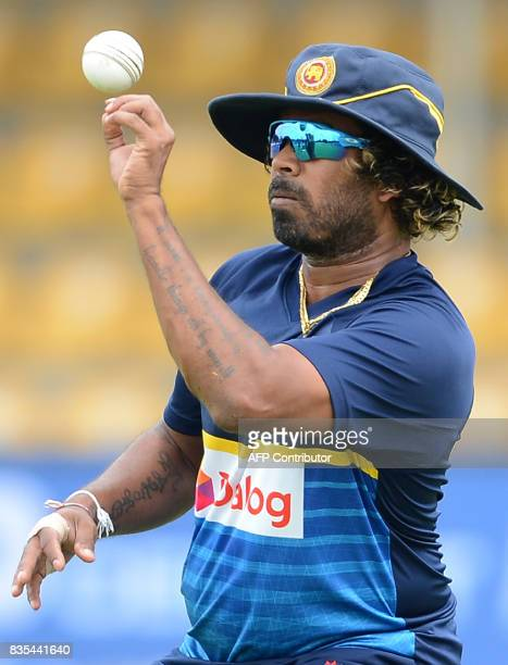Sri Lankan cricketer Lasith Malinga drops a catch during a practice session at the Rangiri Dambulla International Cricket Stadium in Dambulla on...