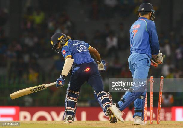 Sri Lankan cricketer Lasith Malinga gets dismissed by Indian cricketer Kuldeep Yadav as wicketkeeper Mahendra Singh Dhoni looks on during the fourth...