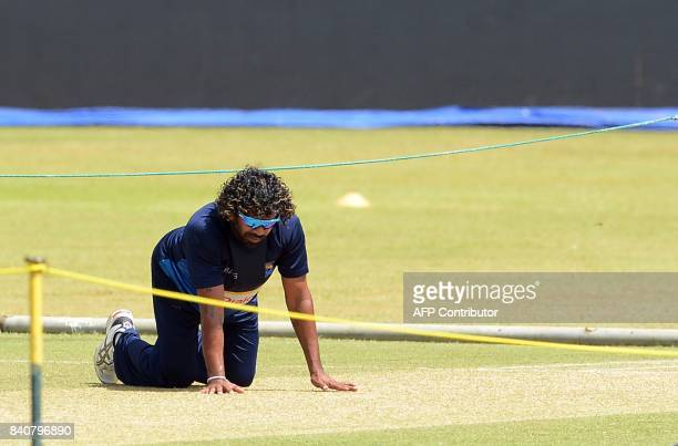 Sri Lankan cricketer Lasith Malinga inspect the pitch during a practice session at The RPeremadasa Stadium in Colombo on August 30 2017 The fourth...