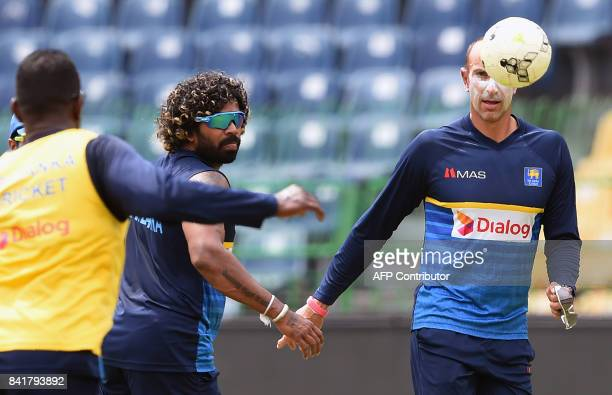 Sri Lankan cricketer Lasith Malinga plays football with coach Nic Pothas during a practice session at RPremadasa Stadium in Colombo on September 2...