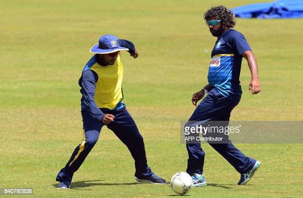 Sri Lankan cricketer Lasith Malinga plays football with teammate Dilshan Munaweera during a practice session at The RPeremadasa Stadium in Colombo on...