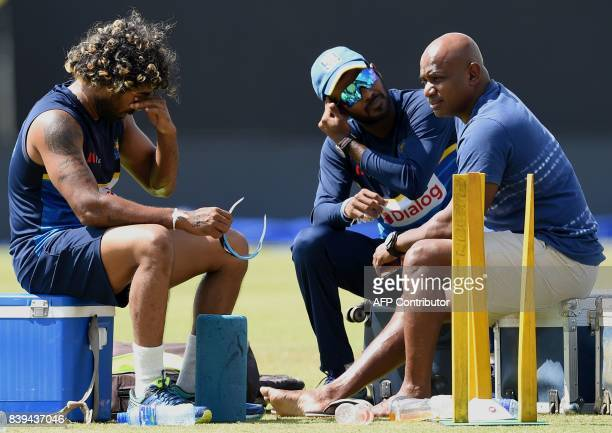 Sri Lankan cricketer Lasith Malinga reacts as the chairman of selectors Sanath Jayasuriya and Upul Tharanga look on during a practice session at the...