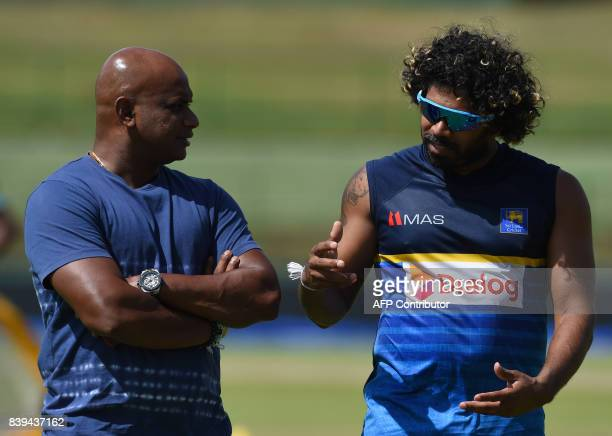 Sri Lankan cricketer Lasith Malinga speaks with chairman of selectors Sanath Jayasuriya during a practice session at the Pallekele International...