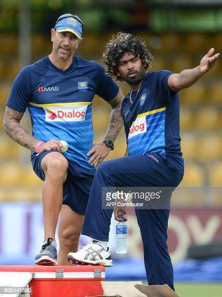 Sri Lankan cricketer Lasith Malinga speaks with coach Nic Pothas during a practice session at the Rangiri Dambulla International Cricket Stadium in...