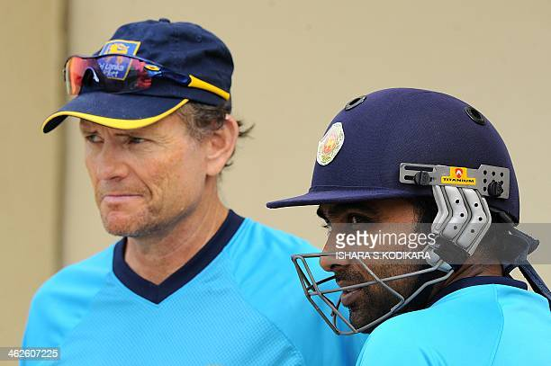 Sri Lankan cricketer Mahela Jayawardene speaks with team coach Graham Ford during a practice session at the Sharjah International Cricket Stadium in...