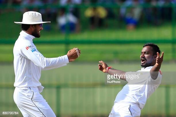 Sri Lankan cricketer Malinda Pushpakumara celebrates the dismissal of Indian batsman Ajinkya Rahane with Sri Lankan cricket captain Dinesh Chandimal...