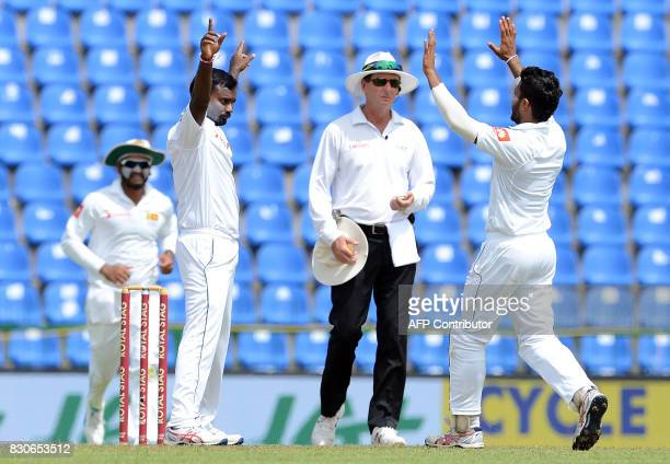 Sri Lankan cricketer Malinda Pushpakumara celebrates with his teammates after he dismissed Indian cricketer Shikhar Dhawan during the first day of...