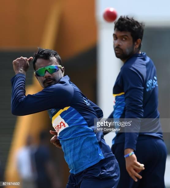 Sri Lankan cricketer Malinda Pushpakumara delivers a ball as Dilruwan Perera looks on during a practice session at Galle International Cricket...
