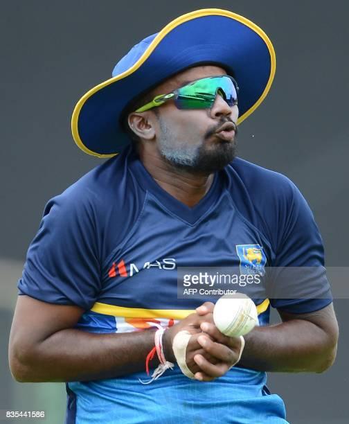 Sri Lankan cricketer Malinda Pushpakumara drops a catch during a practice session at the Rangiri Dambulla International Cricket Stadium in Dambulla...