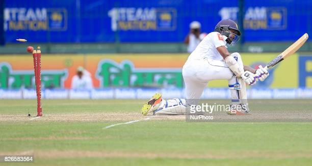 Sri Lankan cricketer Niroshan Dickwella is bowled out by Indian fast bowler Mohammed Shami during the 3rd Day's play in the 2nd Test match between...