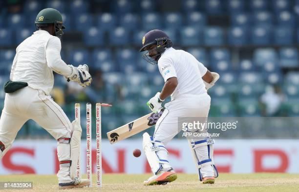 Sri Lankan cricketer Niroshan Dickwella is dismissed by Zimbabwe cricket captain Graeme Cremer as Zimbabwe wicketkeeper Regis Chakabva looks on...