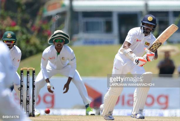 Sri Lankan cricketer Niroshan Dickwella is watched by Bangladesh fielders as he plays a shot during the second day of the opening Test cricket match...