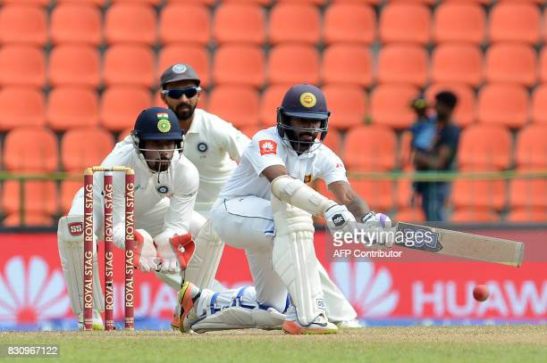 Sri Lankan cricketer Niroshan Dickwella is watched by Indian wicketkeeper Wriddhiman Saha as he plays a shot during the second day of the third and...