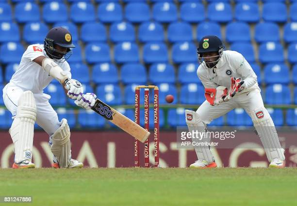 Sri Lankan cricketer Niroshan Dickwella is watched by Indian wicketkeeper Wriddhiman Saha as he plays a shot during the third day of the third and...