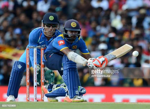 Sri Lankan cricketer Niroshan Dickwella is watched by Indian wicketkeeper Mahendra Singh Dhoni as he plays a shot during the first One Day...