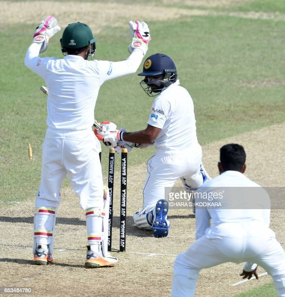 Sri Lankan cricketer Niroshan Dickwella looks back at his stumps after being bowled out as Bangladesh captain Mushfiqur Rahim looks on during the...