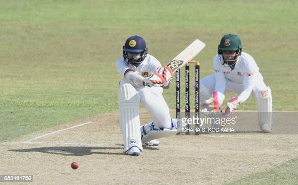 Sri Lankan cricketer Niroshan Dickwella plays a shot as Bangladesh captain Mushfiqur Rahim looks on during the first day of the second and final Test...