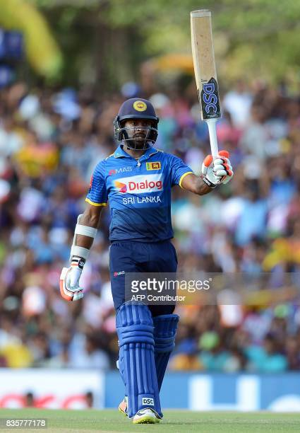 Sri Lankan cricketer Niroshan Dickwella raises his bat to the crowd after scoring a halfcentury during the first One Day International cricket match...