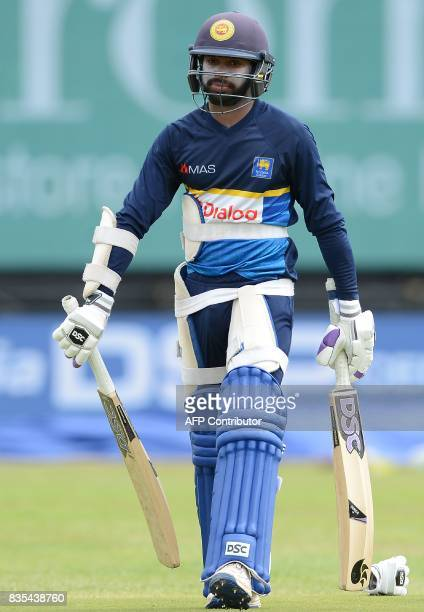 Sri Lankan cricketer Niroshan Dickwella walks to bat during a practice session at the Rangiri Dambulla International Cricket Stadium in Dambulla on...