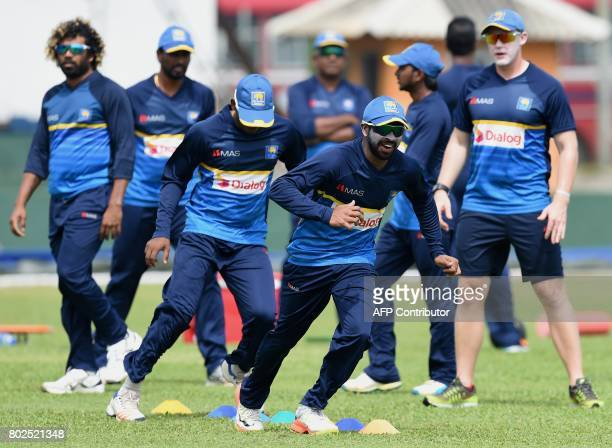 Sri Lankan cricketer Niroshan Dickwella warms up with teammates during a practice session at Galle International Cricket Stadium in Galle on June 28...