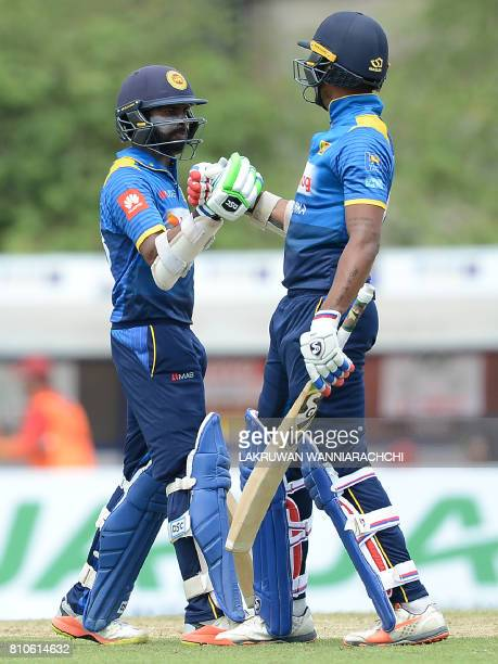 Sri Lankan cricketer Niroshan Dikwella is congratulated by his teammate Danushka Gunathilaka after scoring a halfcentury during the fourth oneday...