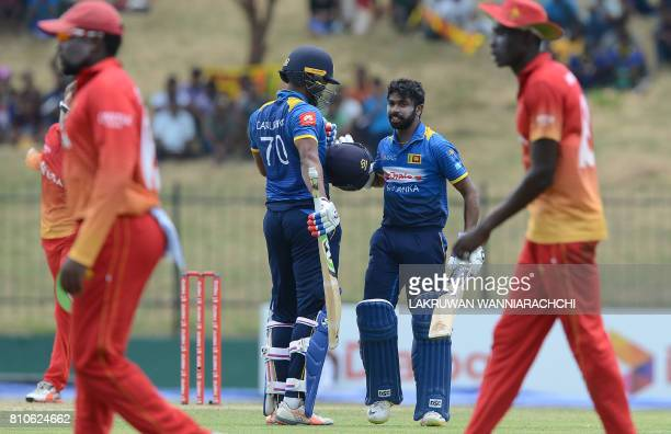 Sri Lankan cricketer Niroshan Dikwella is congratulated by his teammate Danushka Gunathilaka after scoring a century during the fourth oneday...
