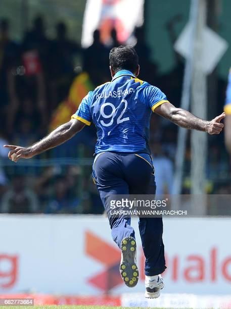 Sri Lankan cricketer Nuwan Kulasekara celebrates after he dismissed Bangladesh batsman Sabbir Rahman during the third and final one day international...