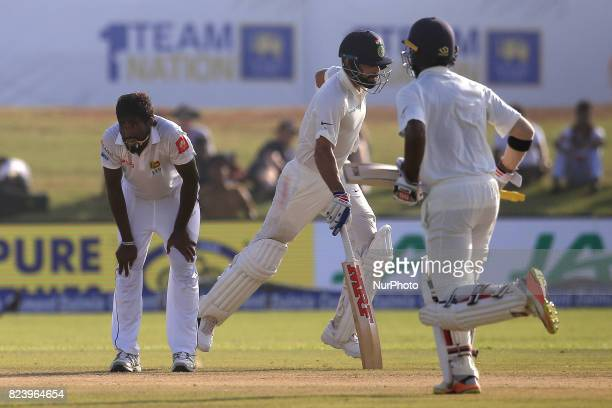 Sri Lankan cricketer Nuwan Pradeep reacts as Indian cricket captain and Indian cricketer Abhinav Mukund run between the wickets during the 3rd Day's...